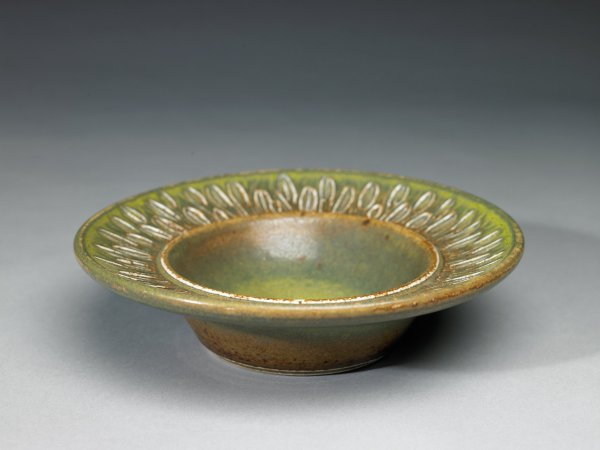Shallow bowl of creamy beige stoneware with a wide rim that is decorated with a stylized leafy pattern, covered with an opaque greenish glaze that varies in shades from light to dark and is flecked brown throughout, occasionally allowing the clay body to show through.