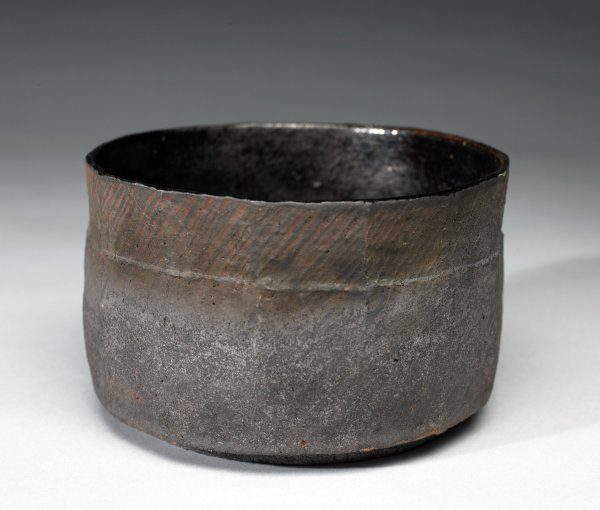 Tall, irregularly shaped bowl of reddish stoneware, Raku-fired creating a scorched, blackish-gray chalky surface, below the rim a series of diagonal lines extending around the body, the interior black.