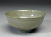 Small footed bowl of rough, grainy green stoneware with a smooth opaque gray-green glaze that covers all but the foot.