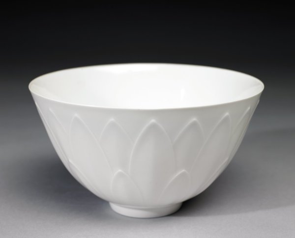 Delicate simple bowl of white porcelain on small, narrow foot, the body decorated in a molded pattern of overlapping stylized leaf elements in varying sizes.
