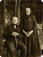 An man is seated with his hands resting on a walking stick between his legs. To his right, his wife is standing with her hands held before her body. Both wear formal clothes and look directly into the camera.  A forest is in the background.