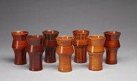 The egg cup has a waisted form that extends upward and flares out, in, and out again to form the lip of the cup. The cups are glazed and shift in color from a light brown to a dark brown. The egg cups are decorated with irregular lines (either dark or light brown) that extend horizontally around the form. The egg cups have a flat lip. The interiors of the cup are also glazed and feature similar horizontal lines that correspond in placement with the exterior. The bottom of the base is unglazed off-white stoneware.