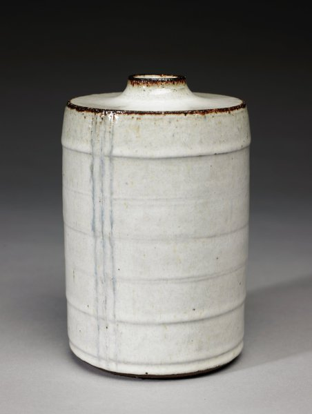 Tall vase of red earthenware, the body cylindrical and covered with a thick, opaque whitish glaze, the body of the vase with a series of striations encircling the body at regular intervals, with long streaks of a darker, bluish glaze down the side, the shoulder is wide and the neck short and squat, the edges of the neck and shoulder as well as the foot rubbed glaze free allowing the red clay to show through.