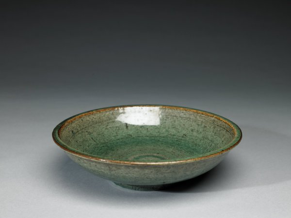 Large, heavy bowl of coarse beige/brown stoneware, covered with a gray-green glaze that is mottled, letting the color of the clay show through, the central well with a scrolled design in the glaze, the rim of the bowl rubbed free of glaze.