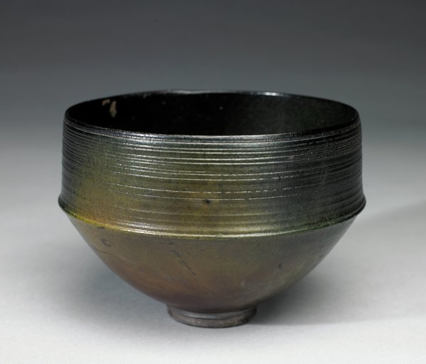 Small bowl of dark stoneware, the shape wide at top and narrowing to a small, round foot, the upper body with incised lines running around it, the lower body smooth, raku glazed and fired to create a surface in mottled shades of brown and black, the foot left glaze free
