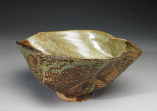 Large bowl on smallish round foot, the body constructed of different thin slabs of clay which overlap to form the bowl creating an irregular, somewhat pointy but graceful body, glazed in various mottled shades of brown, tan, ocher, and gray green.