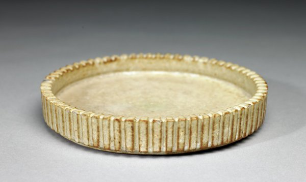 Shallow, round dish of reddish-beige stoneware covered with an opaque, creamy beige glaze which in places allows the color of the clay to show through, the short edge of the dish is fluted.