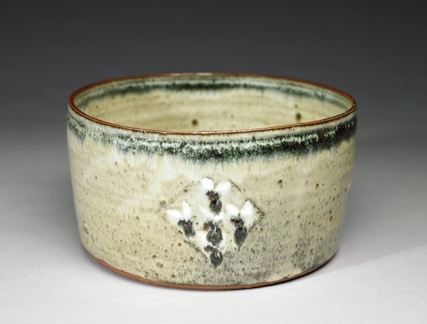 Large, slightly irregularly shaped, round bowl of reddish earthenware covered with a gray-beige glaze that is unevenly applied and contains numerous glaze flaws, the upper outer and inner rims with a band of blue glaze that flows slightly creating a feather-like edge and is partially covered by a white glaze that drips downward, the edge of the rim and foot left glaze free , the body contains on one side a decorative motif consisting of a triangle with five bluish dots surrounded by white bits of glaze.