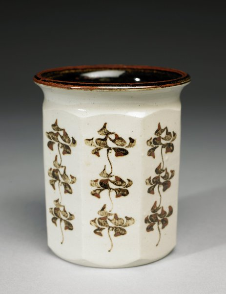 Octagonal vase with clipped shoulder and flared lip, made of creamy beige, smooth stoneware covered on the interior with a mottled brown glaze and on the exterior with a clear glaze that allows the color of the clay to show through, each of the eight panels on the body decorated with brown glaze in a pattern of stylized leafy motifs.