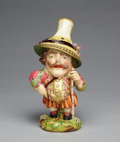 """Soft-paste porcelain figure of a so-called """"Mansion House Dwarf"""" or """"Dwarf Crier"""" standing in full figure on a round, grassy base and wearing black shoes with pink ribbons, a striped pantaloons with floral doublet and pink sleeves, with gilded highlights, holding a staff in his left hand, with large brown mustache and wearing a tall conical hat with narrow brim highlighted in gold and with a black ribbon, the top of the hat has a piece of newsprint with advertisements."""