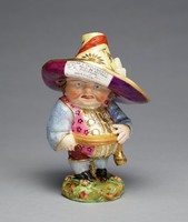 """Soft-paste porcelain figure of a so-called """"Mansion House Dwarf"""" or """"Dwarf Crier"""" standing in full figure on a round, grassy base and wearing black trousers and shoes, pink vest with floral motifs, a brown waist band, blue sleeves and stockings, and a large Dutch cap with upturned brim, ribbons and gold highlights, the underside in purple lustre and with an advertising newsprint on the up turned brim of the hat advertising farm implements."""