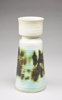 Heavy cylindrical vase that tapers inward and then flares out towards the base. The vase has a white glaze and irregular raised, horizontal lines that continue down the form. The body is decorated with light blue and black splotches around the form that are tinged green, appearing almost like scorch marks on the vase. The vase's lip flares up and out slightly and the upper part of the vase's interior is glazed light blue. The rest of the vase's interior is unglazed.