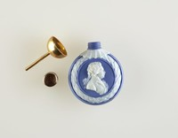 """Round blue jasper perfume bottle with white relief profile portrait of George III, Prince of Wales on one side, on the other three feathers with ribbon inscribed """"ICH DIEN"""" (""""I Serve"""") the motto of the Prince of Wales, with gold cap and funnel"""