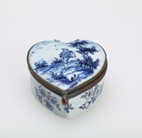 Small enameled copper snuff box in the shape of a heart, with white ground and blue landscape scene with the figure of a male musician on the lid and simple floral elements on the sides.