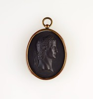 Oval black basalt medallion with relief profile portrait of Caligula, set in brass with ring to hang as pendant