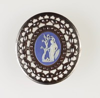 Oval blue jasper cameo with white relief of figure holding spear, standing under tree with snake at feet, set in cut steel mount as a brooch