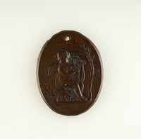 Oval brass medallion with relief of Cupid playing a lyre