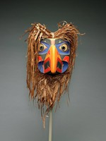 Sculpted zoomorphic mask with curved beak, cedar bark ruff, and painted patterns in orange, red, blue, and black
