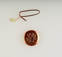 Round jasper cameo with relief of Cupid with bow, soldered to metal wire and dipped in copper