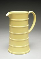 Tall creamware beer jug, Keith Murray shape 3844, with yellow matte straw glaze, slightly flared at the base and decorated with a series of six raised bands running horizontally around the body, with small spout and long ear-shaped handle.
