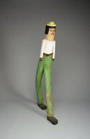 Walking man wearing green pants, white shirt, and yellow hat.