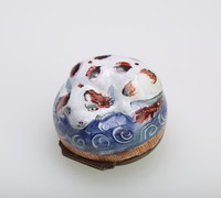Small, round, enameled copper bonbonnière in the shape of a brown and white spotted dog curled up on a blue cushion with orange fringe, the underside painted with a butterfly against a blue and white lattice patterned ground, with gilt metal mounts.