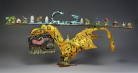 A yellow bird with a long board resting on its head and tail on which are placed ceramic figures of dragons and buildings and a sculpture of a blue cat. From the beak of the bird hangs a painting of a woman and feline.