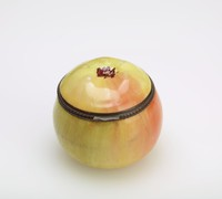 Small enameled copper bonbonnière in the form of a peach or apple in shades of yellow and rust.