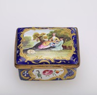 """Small enameled copper box, rectangular, with dark blue ground and gold highlights with reserves on the sides containing small floral sprays, the lid painted in a reserve with the scene of a man and woman with a sheep in wooded landscape, the box inscribed on the inside with the French """"Vous Appas armes mes Bras."""""""