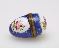 Small nutmeg grater of enameled copper in the shape of an egg, with a deep blue ground and white reserves decorated with floral sprays, inside is a fitted, round grate, with gilt metal mounts.