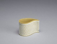 This teardrop-shaped custard cup or dessert pot is made from a fine sheet of moulded yellow jasper which has been decorated with a crenellated edge and the ornamentation of a fine white jasper lattice or trellis design. It was made between 1790 and 1800.