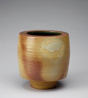 Heavy vase with a barrel shape that tapers in towards the base of the form. The exterior is decorated with impressed bands that begin a third of the way down the form that vary in dimension, gradually diminishing as they continue downward. The body's exterior is primarily an off-white/beige stoneware with darker areas that are rust brown in color. The body is covered in a glaze that gives the stoneware an almost gray cast. This glaze is not even and at several points is interrupted, creating a splotchy effect. The tapered part of the form is primarily rust brown in color, with some lighter, almost orange or tan parts to it. The impressed bands continue once the tapering ends. The bottom of the base is rust brown with a dark tan/mustard center. The lip of the vase extends out from the form towards the center, approximately 2.2 cm. Its outer edge is primarily a dark tan/mustard color that transitions to a rust brown and then a cooler brown. The vase's interior is an irregular dark green color with white lines that correspond in location with some of the exterior's impressed bands.
