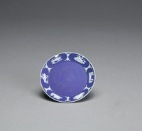 Miniature saucer, or dish, of white jasper with dark blue jasper dip and white relief decoration, around the inner rim a series of tiny relief scenes including Cupid riding a lion; a lion and a calf; Venus and Cupid; a flying Cupid with bow and arrow; and Cupid riding a sea monster.