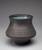 Vase with a waisted form that flares out and then tapers to the base. The exterior is decorated with plain bands circling the form and a central band made up of horizontal, jagged grooves that decrease in size as they move down the vase. The lip of the vase declines inward toward the center of the vase. The vase's interior is glazed gray-blue with a slight green cast to it. The glaze does not extend completely to the bottom of the vase's interior where there are some lumps and areas with no final color glaze. The vase is heavy.