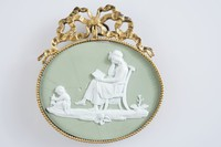 """Oval medallion of white jasper with green jasper dip and white relief with a scene from the """"Domestic Employment"""" series, a seated woman reading and a small child playing with a doll on the floor, mounted in a gilt-bronze frame."""