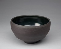 Rotund bowl that tapers to base. The exterior is decorated with plain dimensional bands around the form. There is a slight twisted rop design along the first tapered edge of the bowl. The interior is uniformly glazed black.
