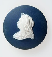 Round dark blue medallion with white relief profile portrait of Queen Victoria (1819-1901) facing left, Queen of Great Britain and Ireland, Empress of India; only child of the Duke of Kent and Victoria Maria Louisa of Saxe Coburg; born at Kensington Palace, 1819. She was crowned in 1838, and in 1840 married Prince Albert of Saxe-Coburg-Gotha by whom she had nine children. Victoria had strong likes and dislikes among the politicians of the day, and although she was, on the whole, a constitutional sovereign, she retained a keen appreciation of her own powers.