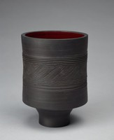 The vase is heavy and has a cylindrical form with a tapered base. The exterior decorated with interspersed dimensional bands. In the center of the vase's body are impressed bands flanking a repeated 's' design imprinted into the form that intersect to create varying shapes. The interior is glazed dark red/plum.