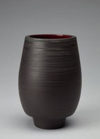 Vase with an elongated cup shape and tapered base. The exterior is decorated with dimensional bands along the vase's form. One thin groove runs along the center of the body, with several shallower grooves as well. The top of the vase has a rougher texture, appears almost sanded. The vase's interior is glazed a dark red/purple with some irregularities.
