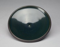 The dish is an open, slightly convex shape. The exterior is matte black with faint line impressions that create a swirl effect with the base's bottom as the center of the swirl. The interior is glazed a dark green and the glaze is smooth and even.