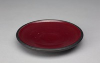The dish is am open, slightly convex shape. Its exterior is decorated with small impressed lines that circle the form. The dish's interior is glazed dark red. There are a couple imperfections in the glaze.
