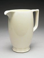 A queensware beer jug, Keith Murray shape 3974, rounded in shape, with large rounded spout, covered in a cream slip-glaze. The jug rests on a faceted foot.