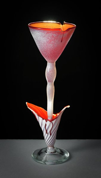 Tall wine goblet with a burgundy bowl, the exterior partially covered with a textured white glass, the lip with two intentional chips from which burgundy-colored glass drips emerge and run down the bowl, the long stem descends into an open burgundy and white flower-like form with similar glass drips and linear threads that spiral to the foot, which is round and of clear glass.