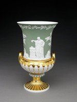 Tall, hard-paste porcelain vase of campana shape, the upper body with white biscuit bas-relief figures against a glazed green ground, the figures include King Friedrich Augustus I of Saxony (1750-1827) dressed as a Roman emperor; he is flanked by the figures of Justice on his right, and Minerva on his left; on the opposite side of the vase is the figure of a Roman vestal, representing the state of Saxony, pouring oil on sacrificial flames on an altar inscribed with the dates of the king's reign; at her feet lies an overflowing cornucopia as well as war trophies and emblems of the seven liberal arts; the bulbous lower body heavily gilt with two handles and a series of applied acanthus leaves of white biscuit porcelain, the foot with central decorative element of green glazed porcelain with small, applied, white biscuit leaves, the lower splayed foot a series of channels