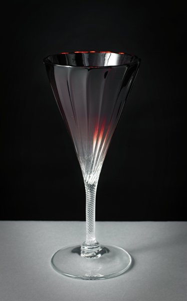 Tall, glass champagne flute with spirally-fluted, conical bowl, in a shade of deep burgundy that fades to light at the bottom of the bowl, the clear glass stem is textured, the round foot also of clear glass.