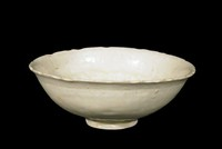 Bowl with carved rim, footring, molded design in cavetto, unglazed stacking ring, cream glaze.