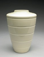 Tapered, shoulder vase, Keith Murray shape 3805, of creamware covered in a champagne slip-glaze. The body has five, engine-turned, parallel lines.  A series of stepped-rings encircle the shoulder, near the mouth. The mouth opens 3 ½ inches in diameter.