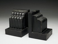 Pair of earthenware bookends, Keith Murray shape 3944, with a black glaze. The bookends are formed by a weighty right-angled base. Within the angle is a curving, double-stepped form, slightly less wide than the main block, and decorated with five concave grooves.