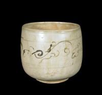Beaker of glazed stoneware with scrolling sprays painted in underglaze-iron.
