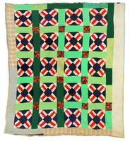 Quilt with red Ts and green stripping.